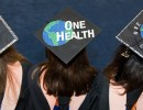3 graduates wearing caps decorated with one health